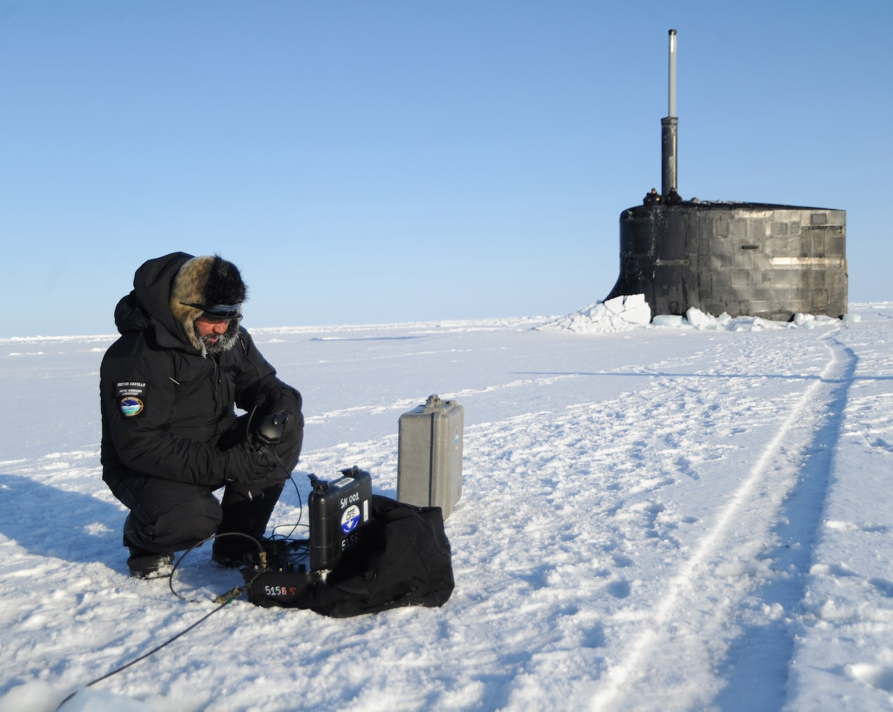A sailor kneels on ice in front of a submarine.