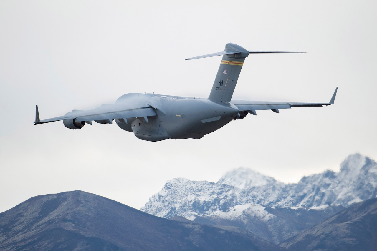 A C-17 Globemaster III flies above snow-capped mountains.