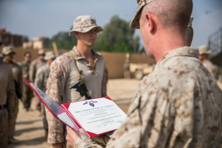 U.S. Marine Corps Sgt. Maj. William Thurber (right), the sergeant major of Marine Corps Forces Central Command, holds the Purple Heart citation for Cpl. Brendon Hendrickson (left), an anti-tank missile Marine with 3rd Battalion, 4th Marine Regiment attached to Special Purpose Marine Air-Ground Task Force, Crisis Response-Central Command, Oct. 22, 2018. Hendrickson received the Purple Heart for wounds sustained in Syria while deployed in support of operations for SPMAGTF-CR-CC.
