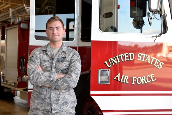 A man wearing the Airman Battle Uniform has his arms folded in front of a firetruck.