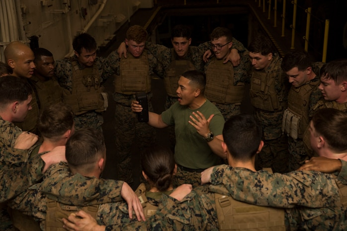 """Cpl. Renilo Maglaya, center, a Marine Corps Martial Arts Program (MCMAP) instructor with Combat Logistics Battalion (CLB) 13, 13th Marine Expeditionary Unit (MEU), leads a """"ring of fire"""" exercise during a MCMAP course aboard the San Antonio-class amphibious transport dock USS Anchorage (LPD 23), Dec. 4, 2018. The Anchorage and embarked 13th MEU are deployed to the U.S. 6th Fleet area of operations as a crisis response force in support of regional partners as well as to promote U.S. national security interests in Europe and Africa."""