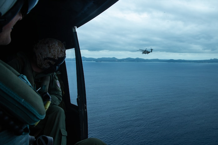 UH-1Y Huey helicopter crew members with Marine Medium Tiltrotor Squadron 262 (Reinforced) watch a CH-53E Super Stallion helicopter in flight during a simulated high altitude, low opening parachute jump and Reconnaissance and Surveillance mission as part of the 31st Marine Expeditionary Unit's MEU Exercise, Okinawa, Japan, Dec. 8, 2018. Marines with the 31st MEU's Amphibious Reconnaissance Platoon specialize in reconnaissance, surveillance and close-quarters tactics during amphibious operations. The 31st MEU, the Marine Corps' only continuously forward-deployed MEU, provides a flexible and lethal force ready to perform a wide range of military operations as the premier crisis response force in the Indo-Pacific region.