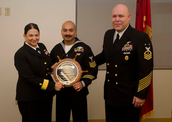 Rear Adm. Tina Davidson, commander of Navy Medicine Education, Training and Logistics Command, and Command Master Chief Petty Officer Richard Putnam, NMETLC, present Petty Officer 1st Class Daniel Guillen, NMTSC hospital corpsman, with a plaque in honor of his selection as NMETLC regional Sailor of the Year Dec 6, 2018, at Joint Base San Antonio-Fort Sam Houston, Texas.