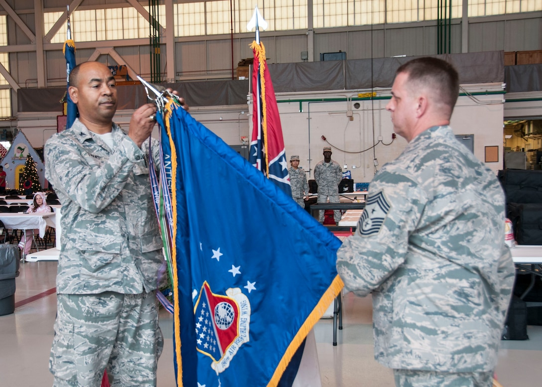 Col. Edward Evans Jr., commander of the 186th Air Refueling Wing (ARW), attaches an Outstanding Unit Award streamer to a ceremonial guidon held by Command Chief Master Sgt. Ronald Arthur, command chief of the 186th ARW, at Key Field Air National Guard Base, Meridian, Mississippi, Dec. 1, 2018. The award was presented during a ceremony to recognize the unit's meritorious service.