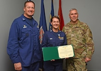 Lt. Brittany Akers, Waterways Mngt, Div. Chief for Coast Guard Sector North Carolina, stands with Wilmington District Commander Col. Robert Clark, right, and Captain Bion Stewart, Coast Guard Sector Commander North Carolina, after receiving the Army Achievment Medal. Lt. Akers completed the U.S. Coast Guard Waterways Management Industry Training while assigned to the Wilmington District's Navigation Branch from May 1 through Oct. 30.