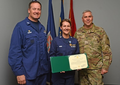 Lt. Brittany Akers, Waterways Mngt, Div. Chief for Coast Guard Sector North Carolina, stands with Wilmington District Commander Col. Robert Clark, right, and Captain Bion Stewart, Coast Guard Sector Commander North Carolina, after receiving the Army Achievement Medal. Akers completed industry training while assigned to the District from May 1 - Oct. 30.