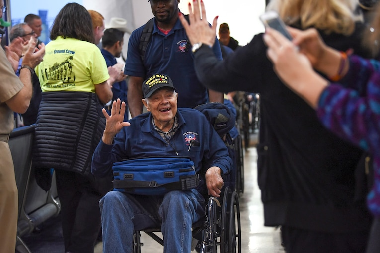 A veteran in a wheelchair smiles and waves to people welcoming him at an airport.