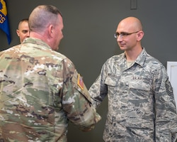 U.S. Army Maj. Gen. Richard Hayes, Jr., left, The Adjutant General for the Illinois National Guard, coins Air Force Master Sgt. Bradley Wheeler, a first sergeant with the 182nd Mission Support Group, in recognition of his outstanding job performance in Peoria, Ill., Dec. 2, 2018.