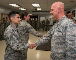 U.S. Air Force Maj. Gen. Ronald Paul, right, The Assistant Adjutant General - Air for the Illinois National Guard, coins Senior Airman Kevin Real, an aerospace medical service specialist with the 182nd Medical Group, in recognition of his outstanding job performance in Peoria, Ill., Dec. 2, 2018.