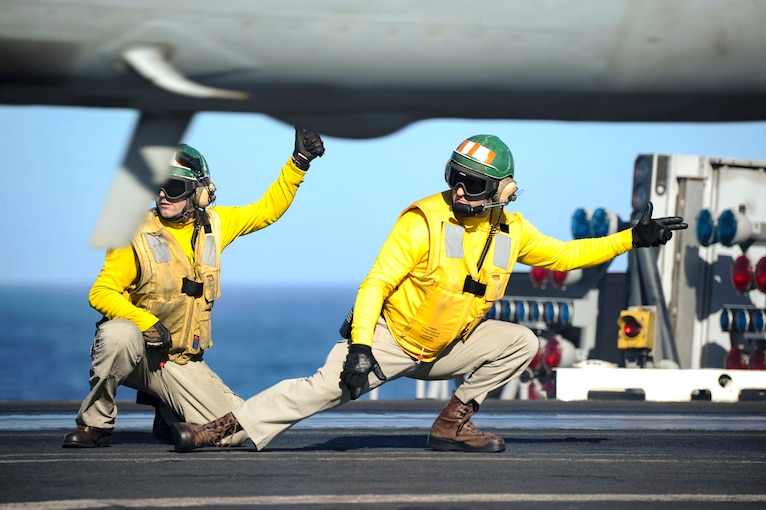 Two kneeling sailors in yellow tops point to launch an aircraft on a flight deck.