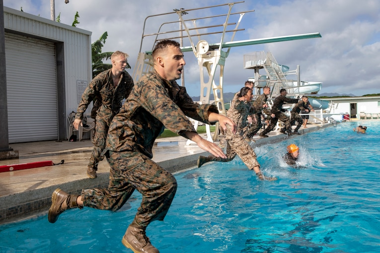 A group of Marines jump into a pool.