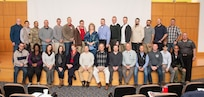 Students of the State Contract Management/Business Manager's Certification Construction Facilities Maintenance Office (CFMO) 102 course pose for a group photo at Camp Dawson, Kingwood, W.Va., Dec. 6, 2018. Students from around the U.S. participated in the course which provided students a deep-dive into contracting topics such as liability claims, bonding and insurance, contract terminations, contractor claims, delays and remedies, payments and closeout, and ethics.