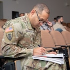 Maj. Juan Rodriquez of the National Guard Bureau Instillations and Environmental office in Arlington, Va., takes notes during a presentation on inspections during the State Contract Management/Business Manager's Certification Construction Facilities Maintenance Office (CFMO) 102 course held at Camp Dawson, Kingwood, W.Va., Dec. 6, 2018. Students from around the U.S. participated in the course which provided students a deep-dive into contracting topics such as liability claims, bonding and insurance, contract terminations, contractor claims, delays and remedies, payments and closeout, and ethics.