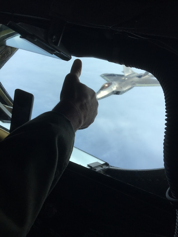 U.S. Air Force Chief Master Sgt. Steven Robinson, boom operator with the 465th Air Refueling Squadron from Tinker Air Force Base, Oklahoma, gives a thumb up to the pilot of an F-22 Raptor Nov. 5, 2018, flying from Tyndall Air Force Base, Florida to Hill Air Force Base, Utah, for depot maintenance.