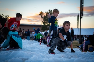 Children play on a pile of snow during Holiday Magic 2018, Dec. 7, 2018, at Luke Air Force Base, Ariz.
