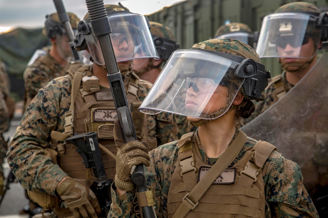 Marines patrol an area with police gear on.