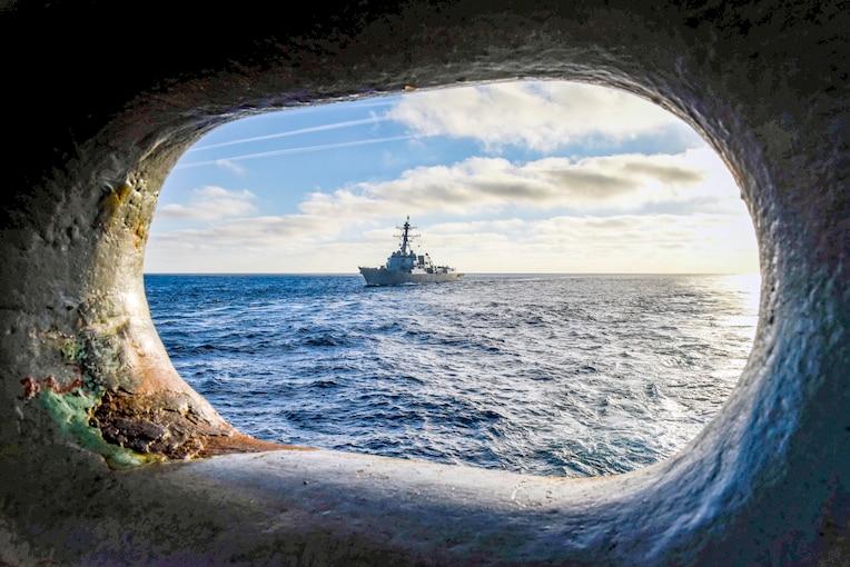 The USS Sherman traverses the open sea, as seen through a window.