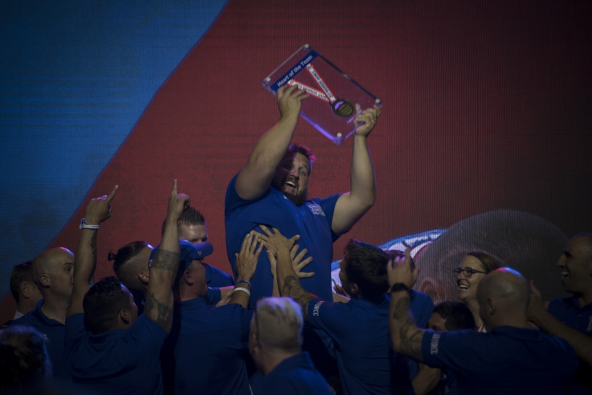 """Rob Hufford, Department of Defense Warrior Games athlete and Team Air Force member, is lifted up by his teammates after being awarded the """"heart of the team"""" award for Team Air Force durinh the Games closing ceremony at the U.S. Air Force Academy, Colorado Springs, Colorado, June 9, 2018. To determine the recipients of the heart of the team award, athletes representing each service team voted for the member of their team who they believe embodies the heart of their team. (U.S. Air Force Photo by Senior Airman Dennis Hoffman)"""