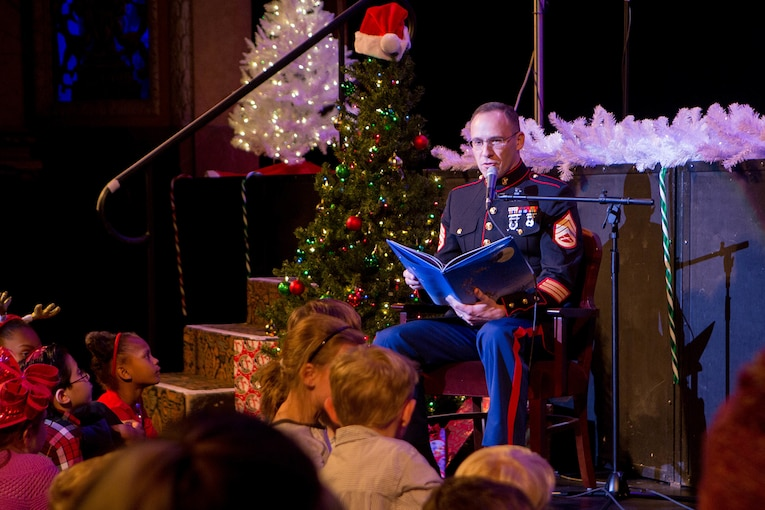 "A service member reads ""'Twas the Night Before Christmas"" to children around a Christmas tree."