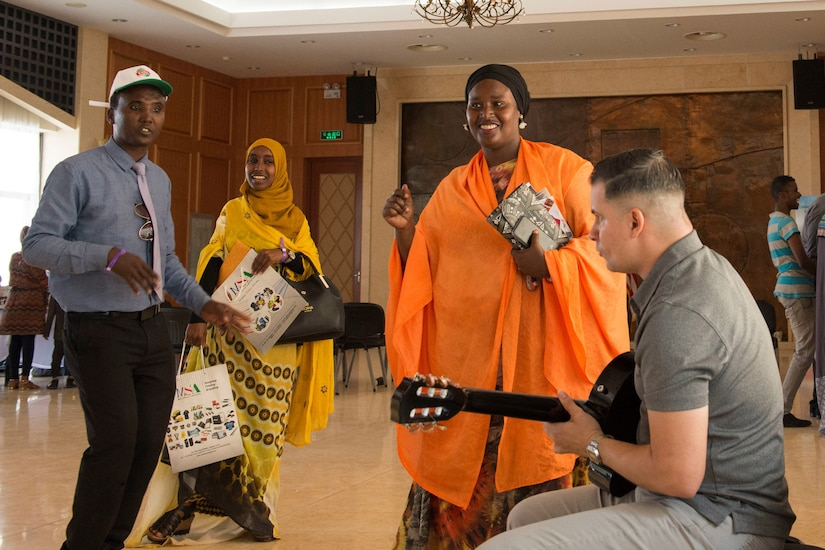 A U.S. service member plays guitar for citizens of Djibouti on the Horn of Africa during a cultural event.