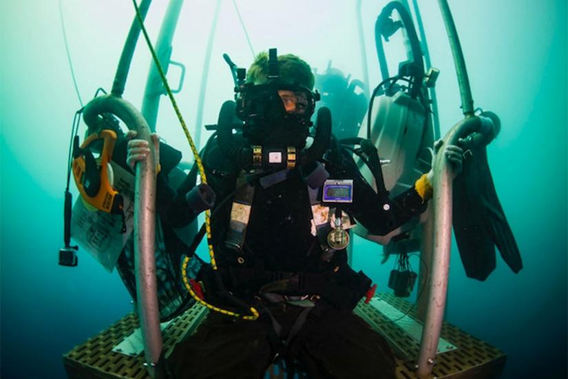 A diver holds onto a platform.