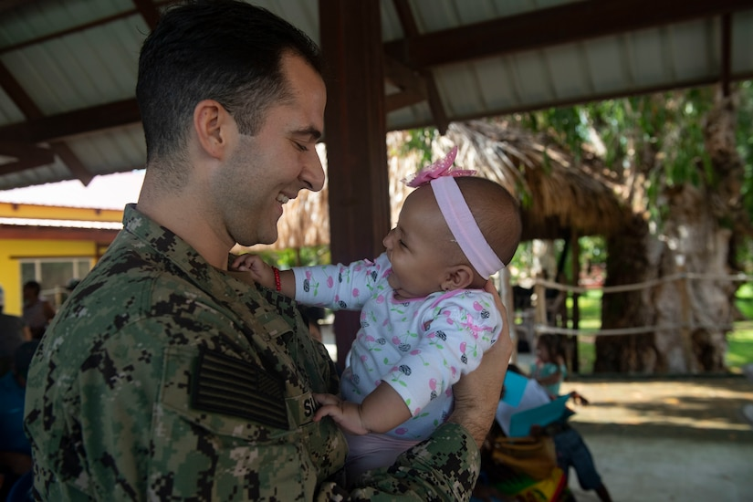 A Navy lieutenant from the USNS Comfort, a hospital shit, holds a baby in Honduras.