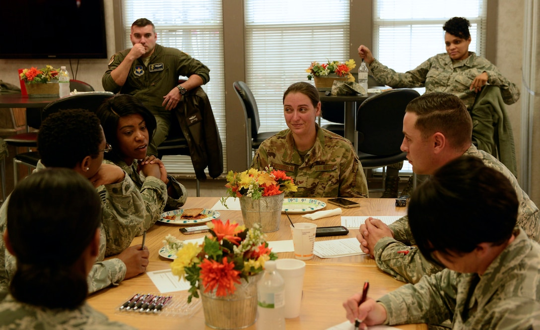 People in uniform sit around a table