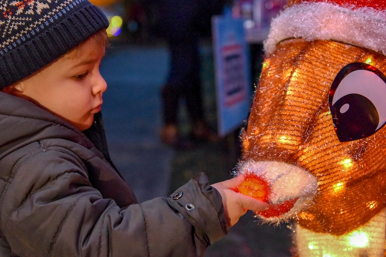 A child squeezes a Christmas decoration's nose.
