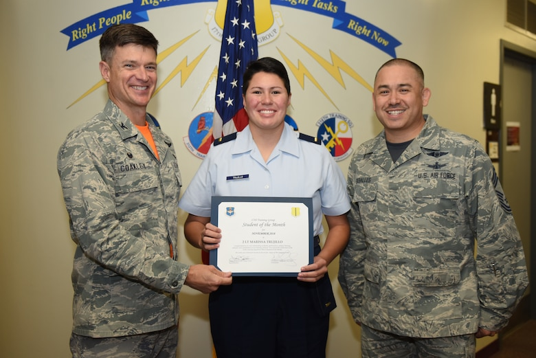 U.S. Air Force Col. Thomas Coakley, 17th Training Group commander, presents the 315th Training Squadron Officer Student of the Month award to 2nd Lt. Marissa Trujillo, 315th TRS student, at Brandenburg Hall on Goodfellow Air Force Base, Texas, Dec. 7, 2018. The 315th TRS's vision is to develop combat-ready intelligence, surveillance and reconnaissance professionals and promote an innovative squadron culture and identity unmatched across the U.S. Air Force. (U.S. Air Force photo by Senior Airman Scott Jackson/Released)