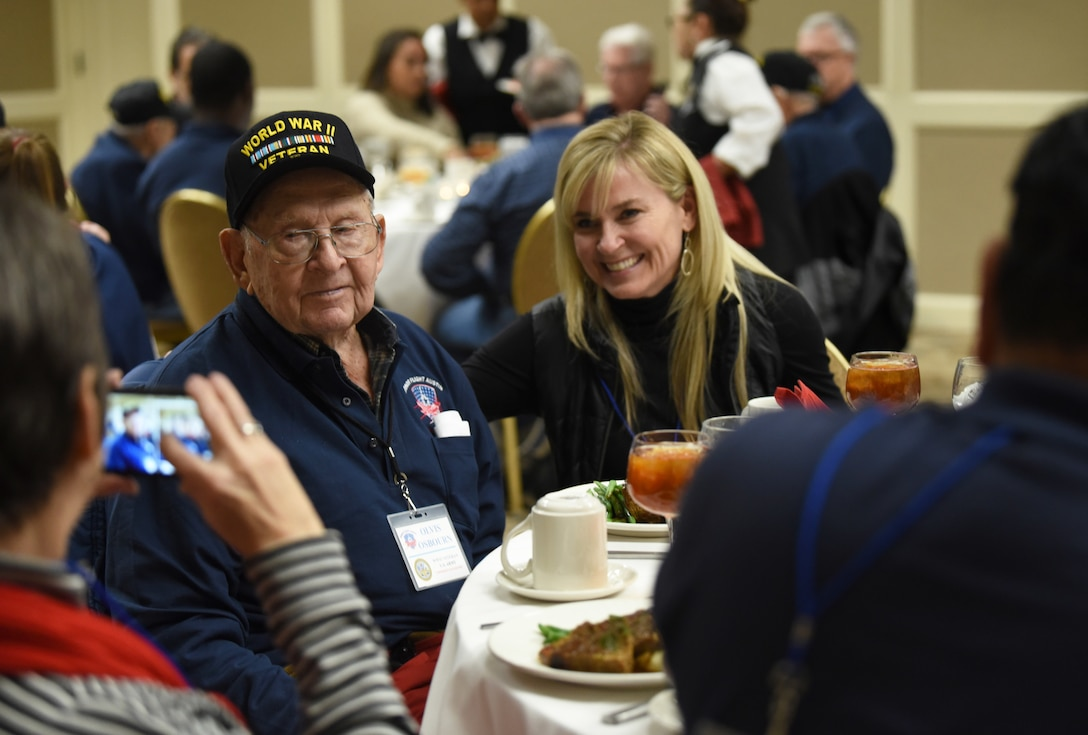 A woman takes a photo of a veteran and another woman at a dinner table.