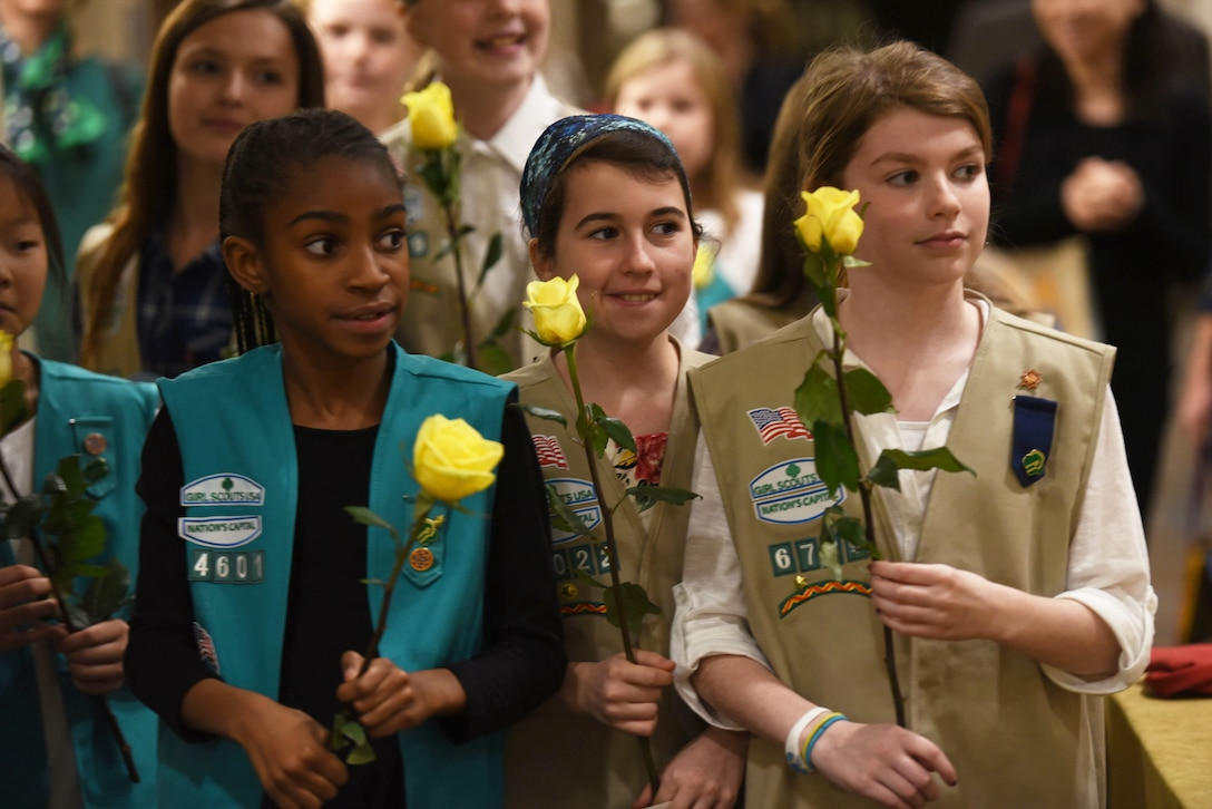 Girl Scouts holding yellow roses stand in a group.