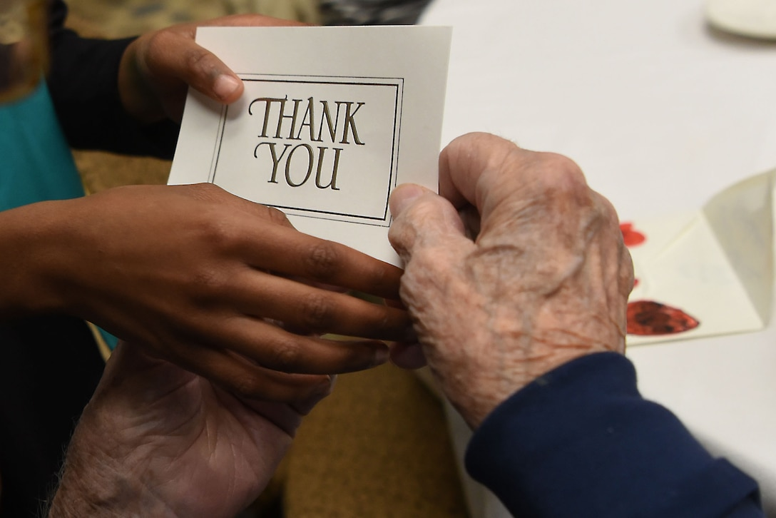 The hands of a child and an old man hold a thank you card.