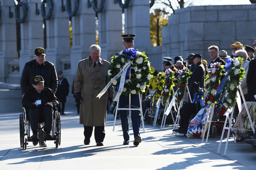 Veterans proceed with a service member carrying a wreath past onlookers during a ceremony.