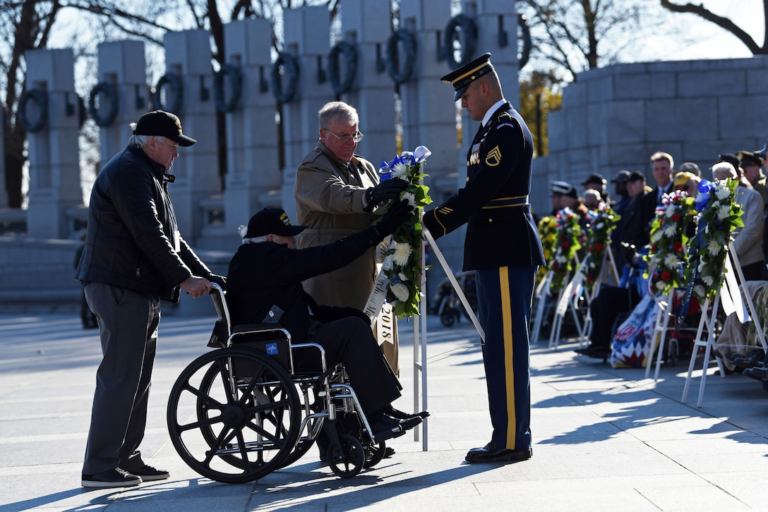 A veteran, a soldier and others place a wreath at the World War II memorial.