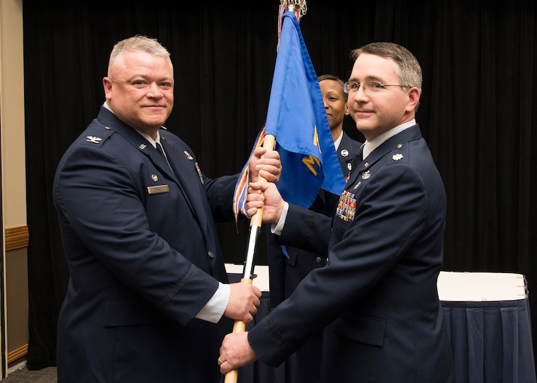 Lt. Col Russell Kohl receives the Medical Group guidon from Col Ken Eaves, 131st Bomb Wing Commander, during the change of command ceremony at Whiteman Air Force Base, Dec. 2. Kohl assumes command from Col. Patti Fries, who continues her military service as the commander of the Nebraska Air National Guard's 155th Medical Group, a subordinate unit of the 155th Air Refueling Wing, at Lincoln Air National Guard Base.  (U.S. Air National Guard photo by Airman 1st Class Joseph Geldermann)