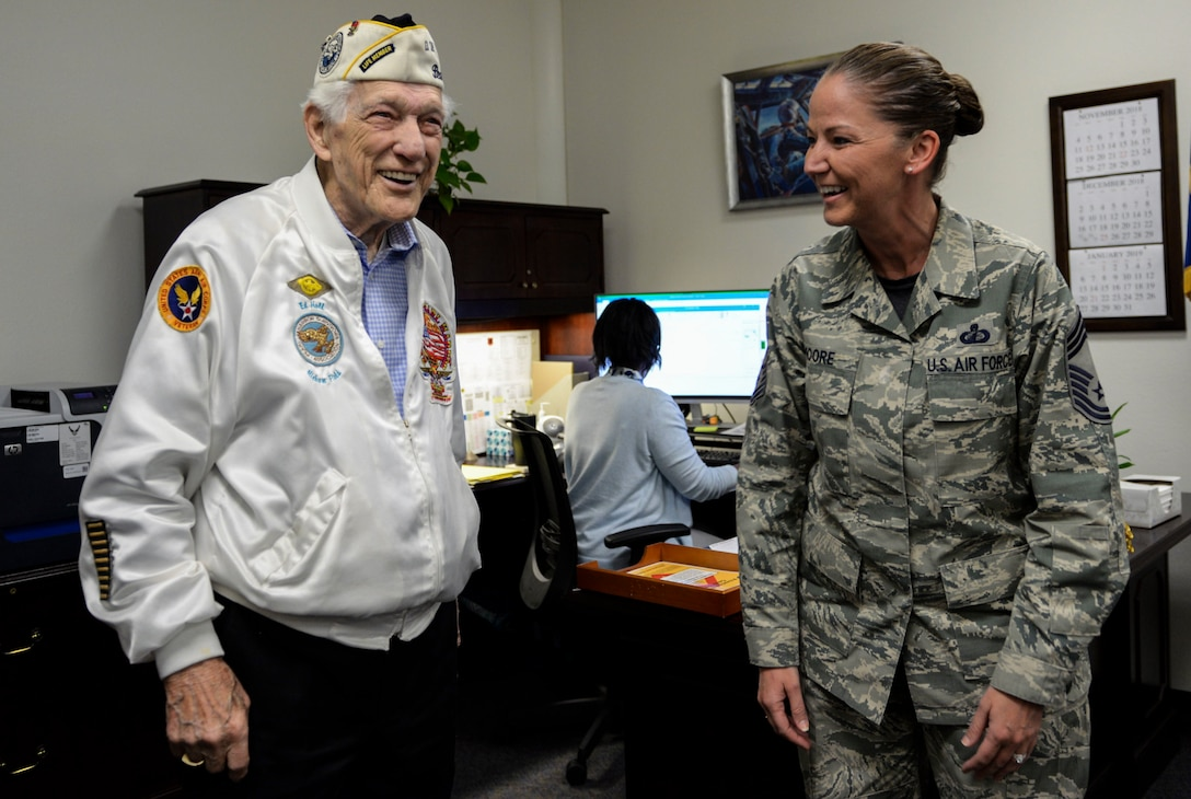 Ed Hall, Pearl Harbor Survivor, laughs with Chief Master Sgt. Tammy Moore, 99th Comptroller Squadron Superintendent, Dec. 7, 2018 on Nellis Air Force Base, Nevada. Hall stopped by the 99th Air Base Wing headquarters to meet with 99th ABW leadership. (U.S. Air Force photo by Airman 1st Class Bailee A. Darbasie)