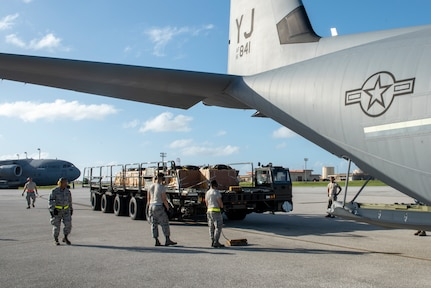 Airmen from 374th Logistics Readiness Squadron position themselves to load Coastal Humanitarian Air Drop (CHAD) bundles on to a C-130J Super Hercules during Operation Christmas Drop 2018 at Andersen Air Force Base, Guam, Dec. 9, 2018. The 374 LRS Combat Mobility Flight work throughout the year to pack the parachutes and build the CHADS in preparation for OCD, supplying the 150 bundles used on training airdrops throughout the event.