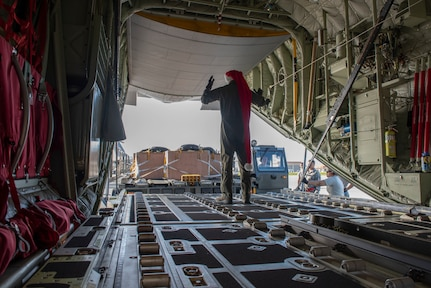 Senior Airman Walter Frank, 36th Airlift Squadron loadmaster, directs an equipment operator from the 374th Logistics Readiness Squadron into position during Operation Christmas Drop 2018 at Andersen Air Force Base, Guam, Dec. 9, 2018. Prior to being loaded onto the planes, the 374th LRS Combat Mobility Flight packs the parachutes and builds the Coastal Humanitarian Air Drop bundles that will be used throughout OCD.