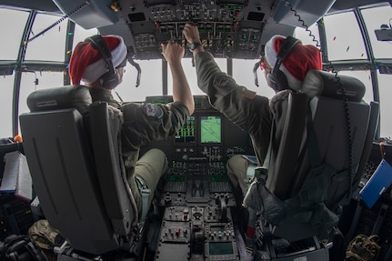Lt. Col. Barry A. King, 374th Operations Group deputy commander, left, and 1st. Lt. Emery Gumapas, 36th Airlift Squadron pilot, right, make adjustments aboard Santa 21 on its way to airdrop supplies to the island of Nama, Federated States of Micronesia during Operation Christmas Drop 2018, Dec. 10, 2018. OCD is a trilateral training mission designed to give C-130 crews from the U.S. Air Force, Japan Air Self-Defense Force (Koku Jietai), and Royal Australian Air Force a chance to airdrop supplies on un-surveyed drop zones throughout the Pacific.