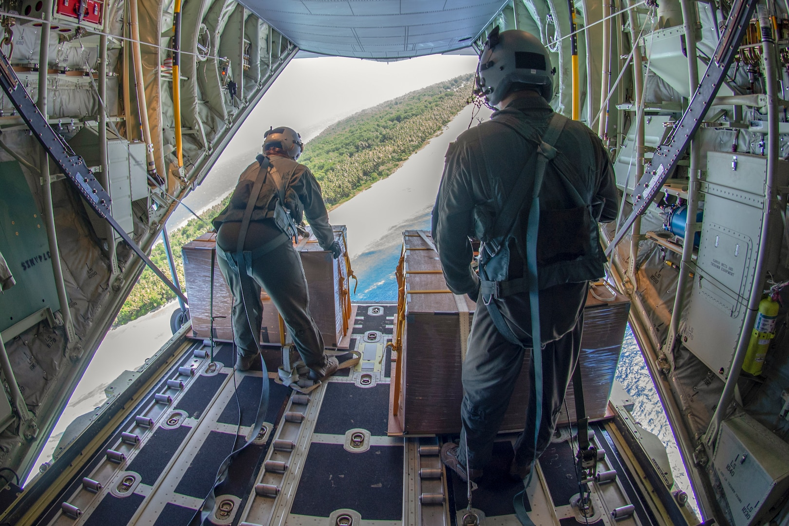 Senior Airman Kylie Hanni, left, and Airman 1st Class Jaime Suarez, right, both 36th Airlift Squadron loadmasters out of Yokota Air Base, Japan, verify their drop zone over the island of Nama, Federated States of Micronesia, during Operation Christmas Drop 2018, Dec. 10, 2018. The flight, carrying Commander, U.S. Indo-Pacific Command, Adm. Phil Davidson and local leaders from the FSM, gave the passengers a firsthand experience into how the aircrews that attend OCD execute the mission. While aboard, Davidson stressed the importance of OCD, a trilateral operation between the U.S. Air Force, Japan Air Self-Defense Force (Koku Jietai), and the Royal Australian Air Force, plays in maintaining the mutual security in the Pacific island chain.