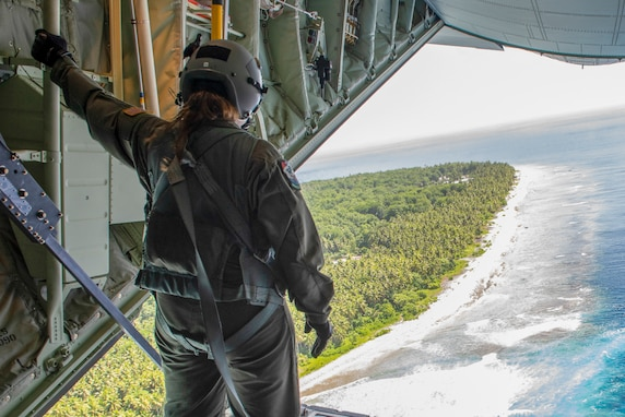 Senior Airman Kylie Hanni, 36th Airlift Squadron loadmaster out of Yokota Air Base, Japan, confirms the airdrop made hit its mark while flying over the island of Nama, Federated States of Micronesia during Operation Christmas Drop 2018, Dec. 10, 2018. In its 67th year, OCD is the world's longest running airdrop training mission providing critical supplies to 56 Micronesian islands impacting approximately 20,000 people across 1.8 million square nautical miles of operating area.