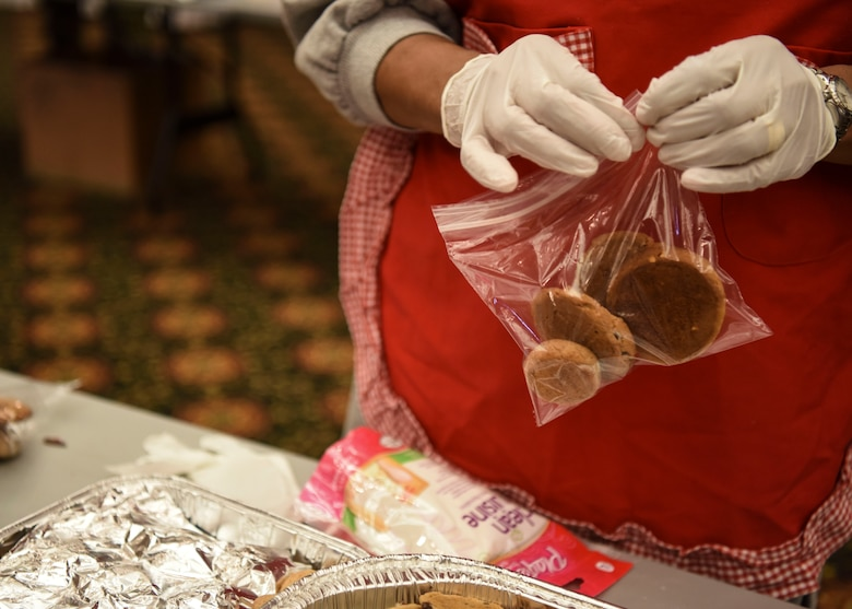 A volunteer bags an assortment of cookies during Operation Sweet Treat at Osan Air Base, Republic of Korea, Dec. 10, 2018. An assortment of four cookies was placed in each bag for the service members to receive for the holidays. The cookies were combined with candy and Moon Pies before being sent out for delivery. (U.S. Air Force photo by Airman 1st Class Ilyana A. Escalona)