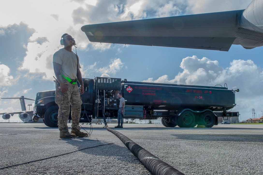 Staff Sgt. Christopher Canto, 374th Aircraft Maintenance Squadron flying crew chief, communicates with the rest of his team aboard a C-130J Super Hercules via radio during the refueling process at Operation Christmas Drop 2018 at Andersen Air Force Base, Guam, Dec. 9, 2018.