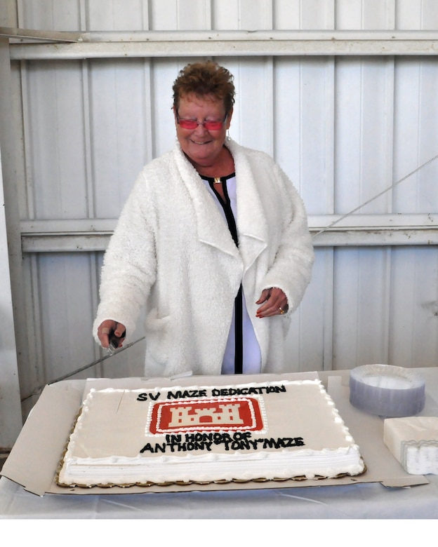 """Gayle Mayes, widow of Anthony """"Tony"""" Maze cuts cake following the Dedication Ceremony for Survey Vessell Maze, Dec. 7."""