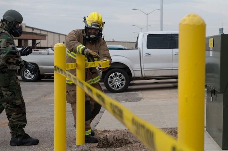 U.S. Air Force Senior Airman Trenton Reddy, a fire protection member assigned to the 97th Civil Engineer Squadron, puts up caution tape