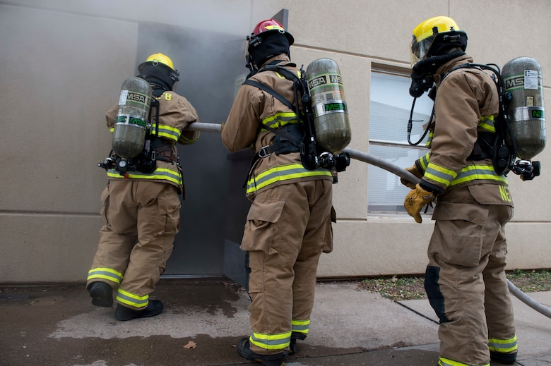 Fire protection members assigned to the 97th Civil Engineer Squadron enter a facility that is filled with imitation smoke