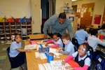 Ryan McLeod, a DLA Troop Support Industrial Hardware branch chief and volunteer, watches students color drawings during the Children's Holiday Party at Benjamin Franklin Elementary School Dec. 6, 2018 in Philadelphia.