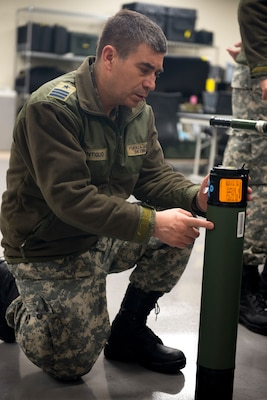 Chilean Air Force Lt. Col. Claudio Montiglio, medical health officer, looks at a Critical Care Air Transport Team's oxygen supply bottle on Dec. 7, at Camp Bramble on Joint Base San Antonio-Lackland, Texas. Each CCATT carries roughly 560 pounds of gear, enough to continue the level of acute care for three critically ill patients up to 24-hours. (U.S. Air Force photo by Kiley Dougherty)