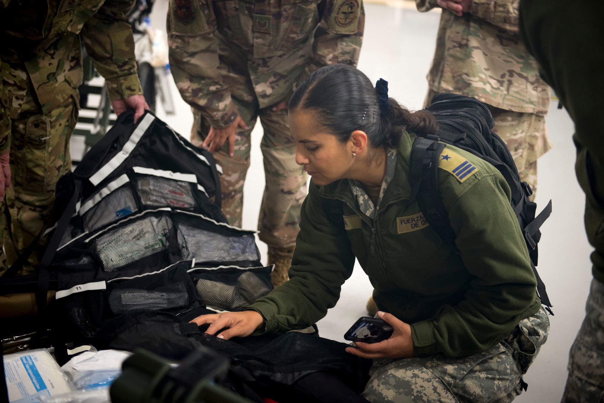 Chilean Air Force Capt. Vivian Leiva, medical health officer, looks through a bag of medical supplies used on Critical Care Air Transport missions on Dec. 7, at Camp Bramble on Joint Base San Antonio-Lackland, Texas. Each CCAT Team carries roughly 560 pounds of gear, enough to continue the level of acute care for three critically ill patients up to 24-hours. (U.S. Air Force photo by Kiley Dougherty)