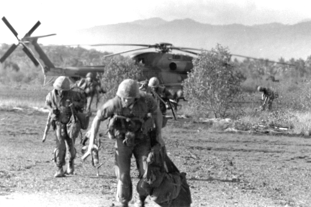 Marines run from helicopter.
